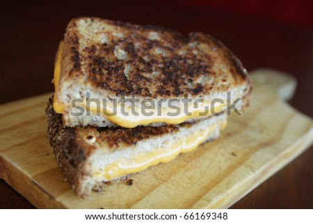 Delicious sandwich with melted orange cheese on a cutting board - stock photo