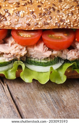 Delicious sandwich with tuna and vegetables on an old table macro. vertical   - stock photo