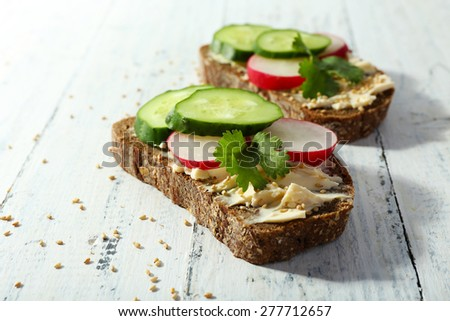 Delicious sandwiches with vegetables and parsley on wooden background - stock photo