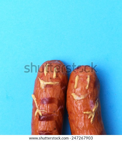 Delicious sausages on a blue background - stock photo