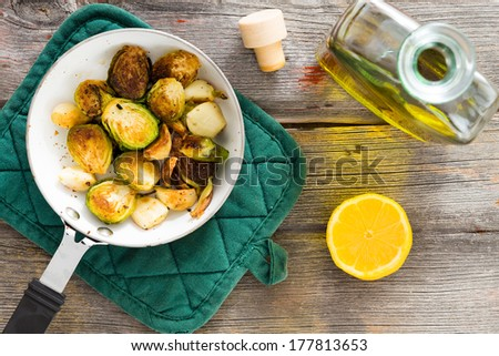 Delicious sauteed brussels sprouts with olive oil and fresh lemon for a tangy zesty flavour in a saucepan on a rustic tabletop in a country kitchen, overhead view - stock photo