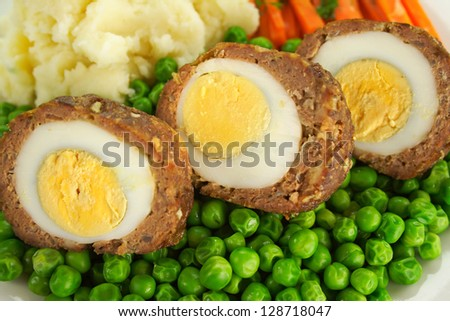 Delicious scotch eggs with peas, carrots and mashed potato. - stock photo