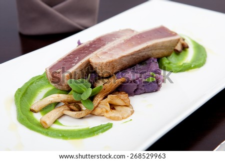 delicious seafood dinner with fillet of tuna, green pea puree, oyster mushrooms and potatoes - stock photo