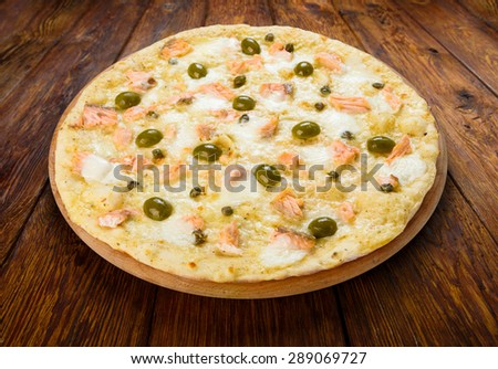 Delicious seafood pizza with salmon, capers and olives - thin pastry crust isolated at wooden background - stock photo