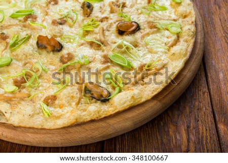 Delicious seafood pizza with shrimps, mussel, olives and leek - thin pastry crust at wooden background, closeup - stock photo