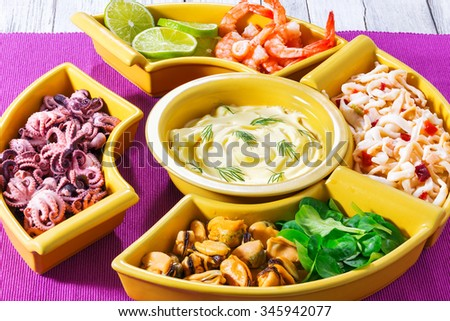 delicious seafood set of prawns, octopus, mussels, squid rings with lime and mung bean green leaves salad with creamy hollandaise sauce and chopstick on the magenta table napkin, - stock photo