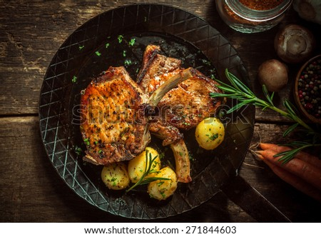 Delicious seasoned pan fried pork cutlets cooked in a spicy marinade and served with boiled baby potatoes in their jackets garnished with rosemary , overhead view with ingredients - stock photo