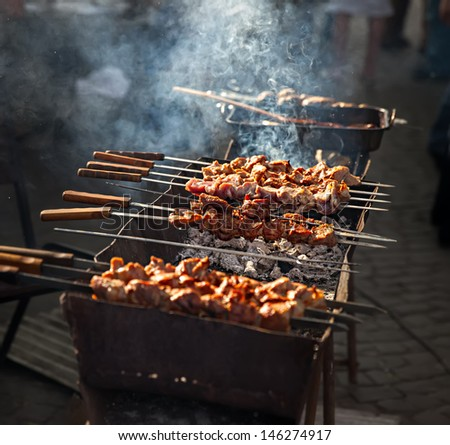 Delicious shish kebab grills on the barbecue in smoke - stock photo