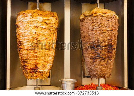 Delicious slabs of skewered fast food shawerma chicken and lamb meat turn side by side on a spit. This is part of a common sandwich found in the Middle East. - stock photo