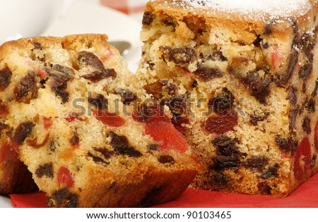 delicious sliced fruit cake with mixed fruit and cherries on a red napkin - stock photo