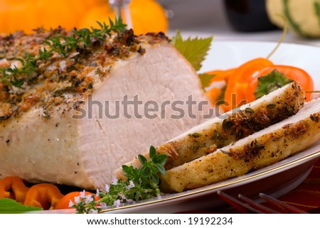 Delicious sliced garlic thyme roast pork loin is ready for dinner in middle of fall arrangement table. - stock photo