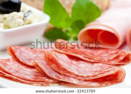 Delicious slices of salami with ham and feta cheese - stock photo
