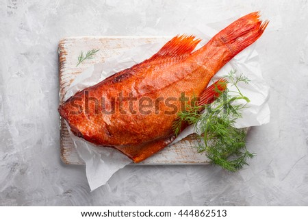 Delicious smoked fish (ocean perch) on wooden background for healthy food, diet or cooking concept, selective focus - stock photo