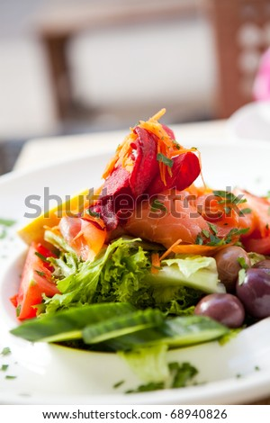 Delicious smoked salmon salad on an outdoor restaurant table - stock photo