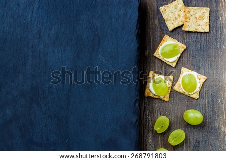 Delicious soft cheese crackers with grapes on slate and wooden background. Vegetarian food, health or diet concept. Top view. - stock photo