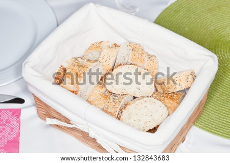 Delicious sourdough bread in a backet on party table. - stock photo