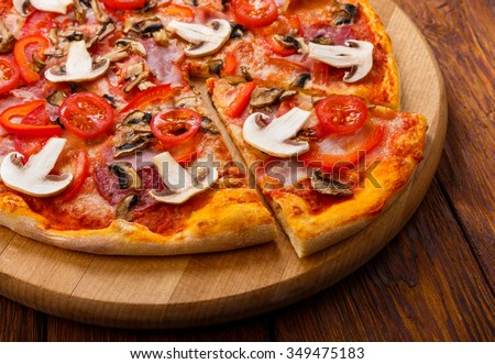 Delicious spicy pizza with mushrooms, peppers, ham, cherry tomatoes and pepperoni - thin pastry crust piece cut, closeup on wooden round desk at wooden background - stock photo