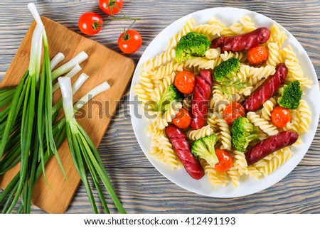Delicious Spiral Pasta salad with  broccoli, grilled sausages  and tomatoes on a  dish,  spring onions on a cutting board, top view - stock photo