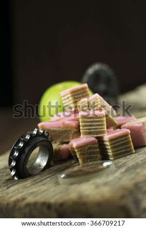 Delicious stack of several sweet cookies on wooden table with gear wheel - stock photo