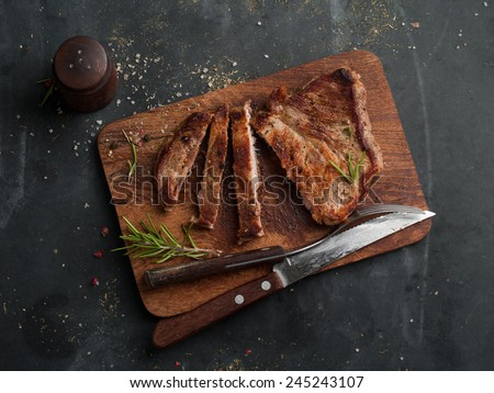 Delicious steak on wooden board, selective focus - stock photo