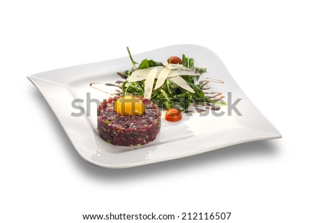 Delicious Steak tartar with yolk and rocket salad ready to serve isolated on white plate - stock photo