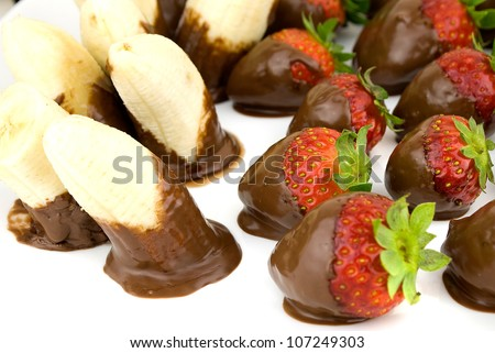 delicious strawberries and bananas covered with chocolate in a white plate - stock photo