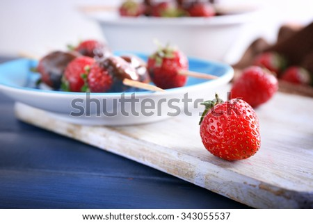 Delicious strawberries in chocolate on kitchen table - stock photo