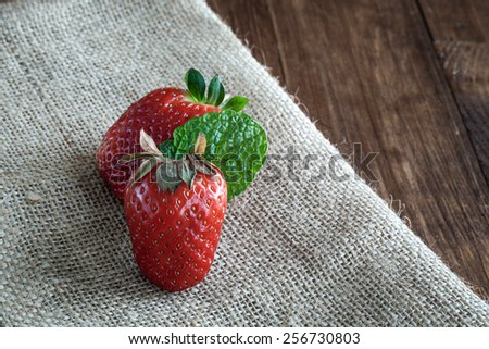 Delicious strawberries in white bowl on wooden table - stock photo