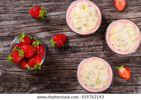 delicious strawberry cheesecake mousse cups decorated by homemade ice cream on an old rustic wooden table, view from above  - stock photo