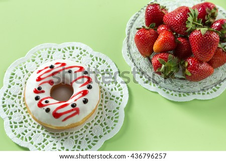 Delicious strawberry donut, served on a white napkin, decorated with strawberry.Green background. Horizontal image. - stock photo