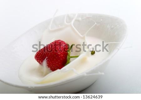 Delicious strawberry splashing into cream - stock photo