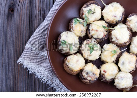 Delicious stuffed mushrooms with meat and cheese in brown ceramic dish on old wooden background - stock photo