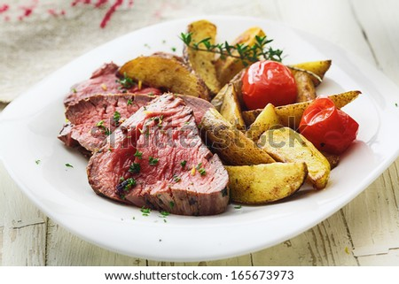 Delicious succulent rare beef steak sliced and served with roast potato wedges and tomato garnished with chopped parsley - stock photo