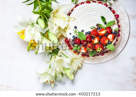 Delicious summer cake with berries and meringue on white wooden background. Homemade cake. Pavlova meringue cake with cream and berries - stock photo