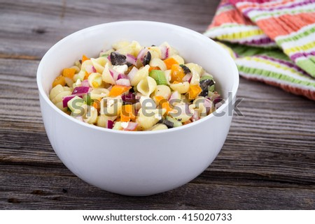 delicious summer pasta salad on rustic table with feta and red onion - stock photo