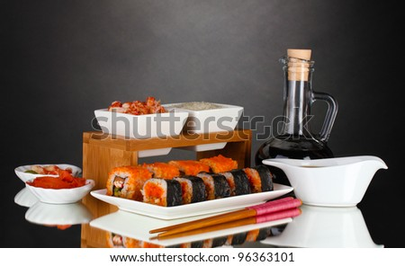 delicious sushi on plate, chopsticks, soy sauce, fish and shrimps on gray background - stock photo