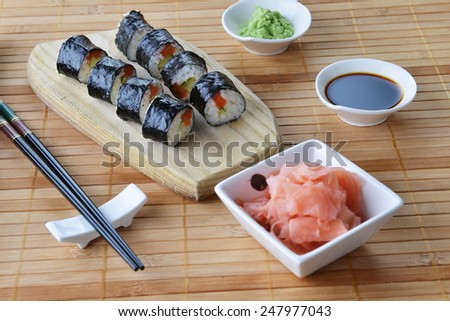 Delicious sushi rolls on wooden background - stock photo