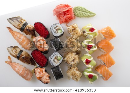 Delicious sushi rolls set with wasabi and marinated ginger. On a table as a background. - stock photo