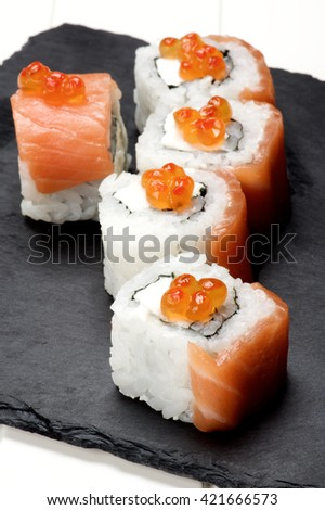 Delicious Sushi with Smoked Sliced Salmon and Gourmet Red Caviar on Stone Plate closeup on White Plank background - stock photo