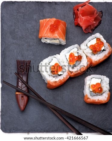 Delicious Sushi with Smoked Sliced Salmon and Gourmet Red Caviar on Stone Plate with Chopsticks and Ginger closeup on White Plank background - stock photo