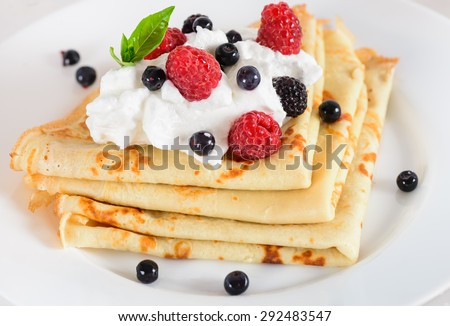 Delicious sweet crepes decorated air cream and ripe berries, raspberries, blackberries and blueberries on a white plate. Tasty breakfast. - stock photo