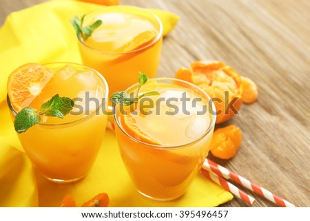 Delicious tangerine cocktails with ice and a mint on a yellow napkin, close up - stock photo