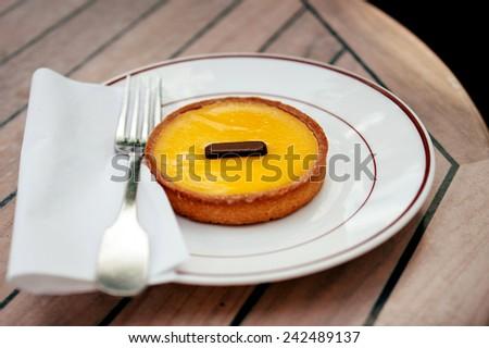 Delicious tarte au citron (lemon tart) on plate in a Parisian cafe. Tilt-shift lens used for better image  - stock photo