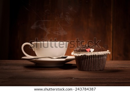 Delicious tasty cupcake and coffe cup on wooden table - stock photo
