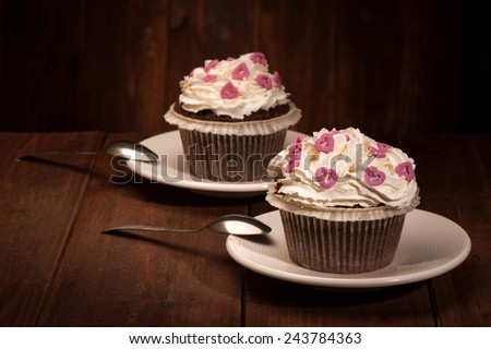 Delicious tasty cupcakes on wooden table - stock photo