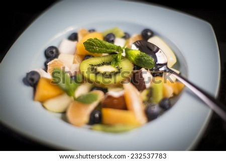 Delicious tasty exotic fruit salad with black background - stock photo
