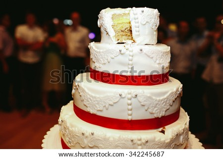 Delicious tasty layered white wedding cake with red ribbons ornated closeup - stock photo