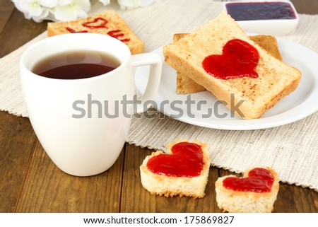 Delicious toast with jam and cup of tea on table close-up - stock photo