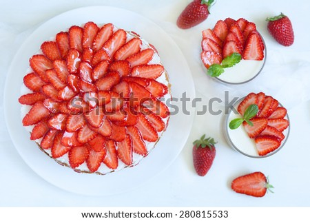 Delicious traditional celebration strawberry cake sweet dessert food with fresh strawberries on white kitchen table background. Rustic view and natural light. Top view. - stock photo
