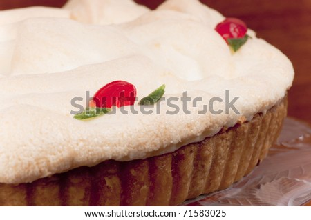 Delicious traditional homemade lemon ,meringue tart  on a glass cake stand, decorated with red cherries and green angelica. - stock photo